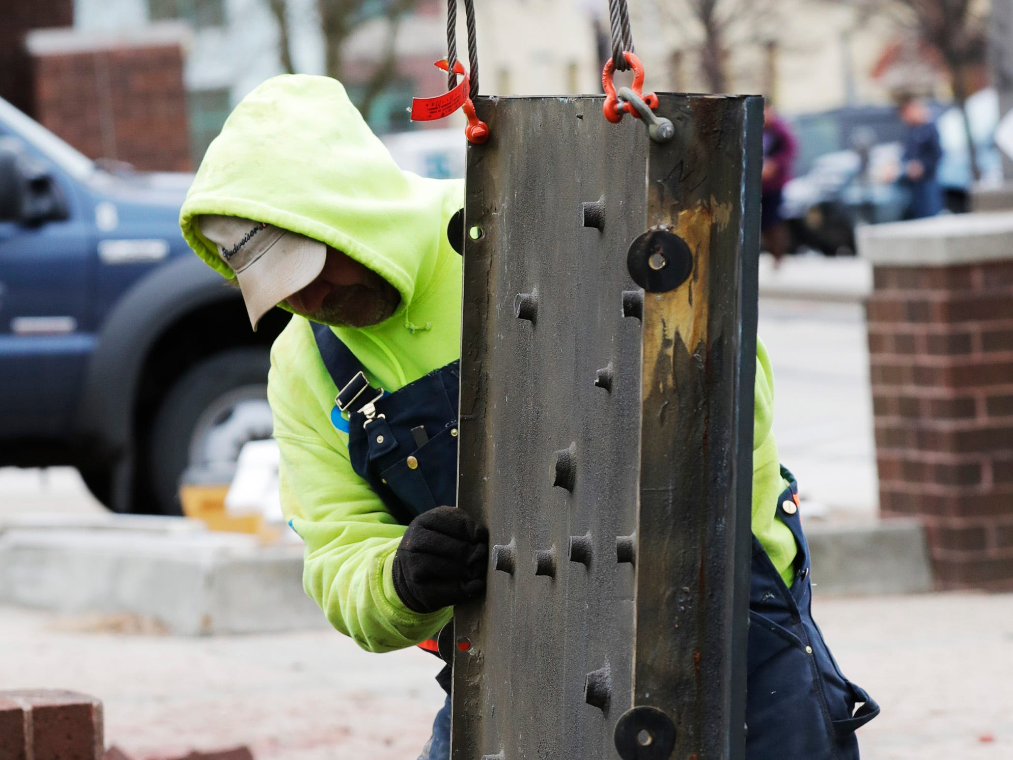 A Koenig Constructions guides a cast panel after removal from the clock tower at Mead Public Library, Wednesday April 10, 2019, in Sheboygan, Wis. The city is repurposing the cast panels for an 8th Street display as part of a renovations project.