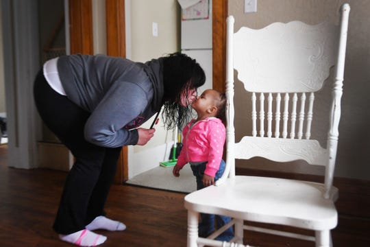 Hanah Christman gives her youngest daughter Aurora a kiss Tuesday, April 9, in their home provided to them by a newÊlocal housing program, One Roof, in Sioux Falls. Christman said she is able to provide a stable life for her children now that they don't have to worry about where they are going to sleep night to night. Christman's two oldest children, not pictured were at school.