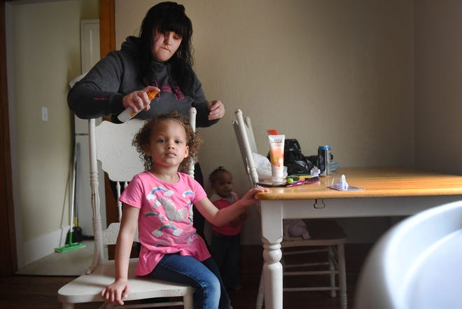 Hanah Christman brushes her daughter Ciara's hair Tuesday, April 9, in their home provided to them by a newÊlocal housing program, One Roof, in Sioux Falls. Christman said she is able to provide a stable life for her children now that they don't have to worry about where they are going to sleep night to night. Christman's two oldest children, not pictured were at school.