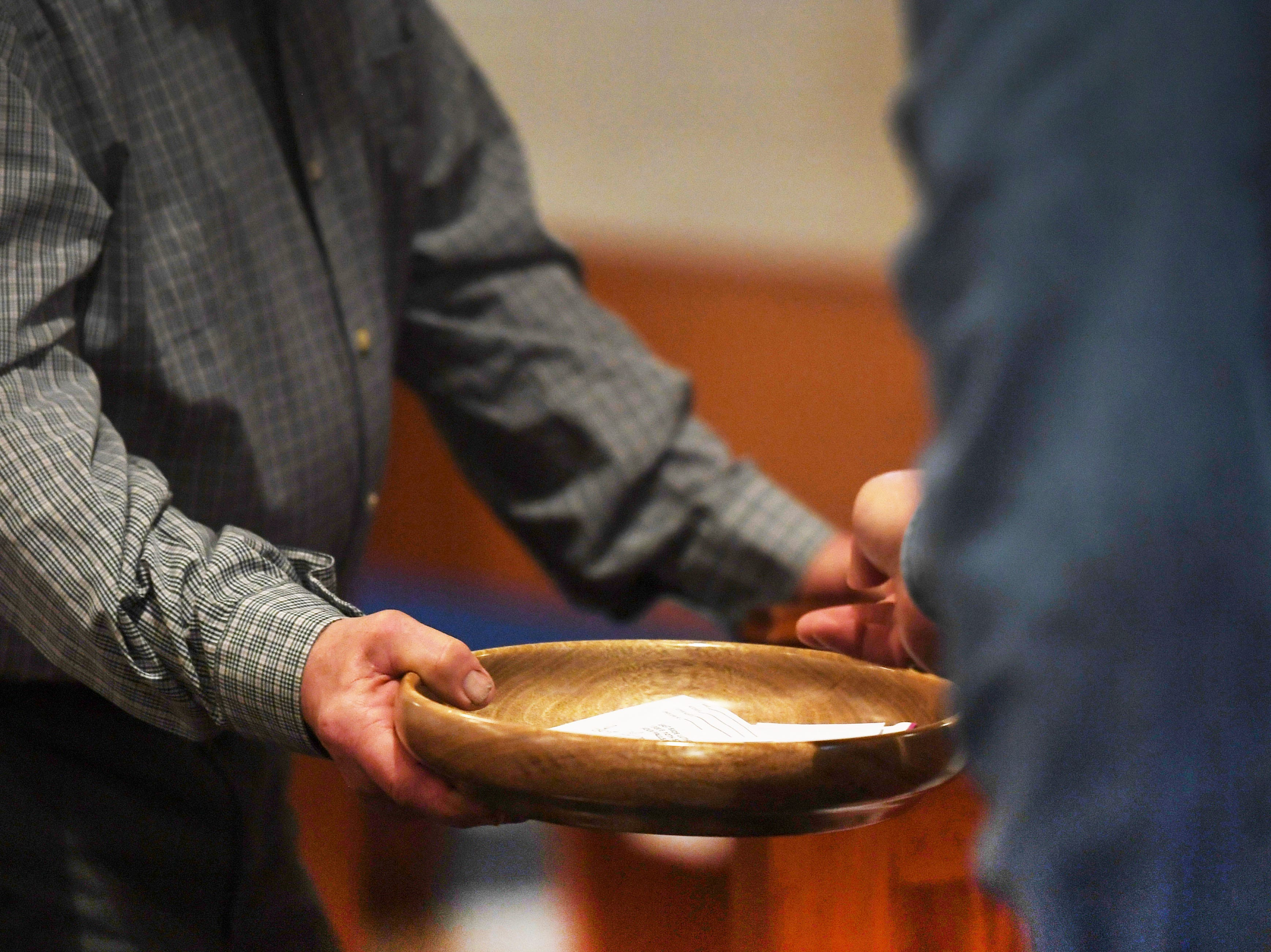 East Side Lutheran Church members give offerings during the noon service Wednesday, April 10, in Sioux Falls.
