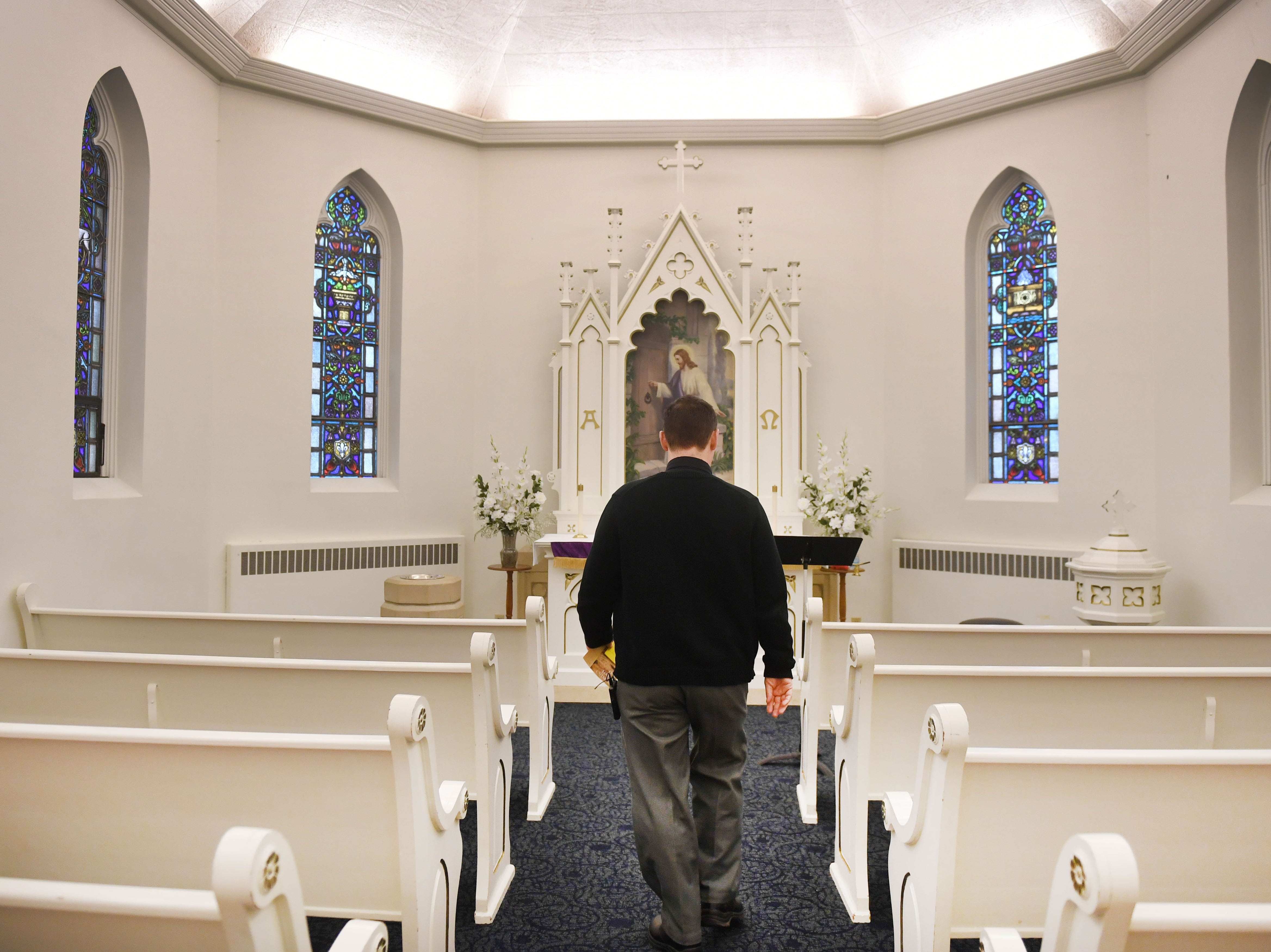 Pastor Layne Nelson walks through the chapel room at East Side Lutheran Church Wednesday, April 10, before noon service in Sioux Falls. Nelson said the alter in the chapel room is the original alter from the original church down the street.