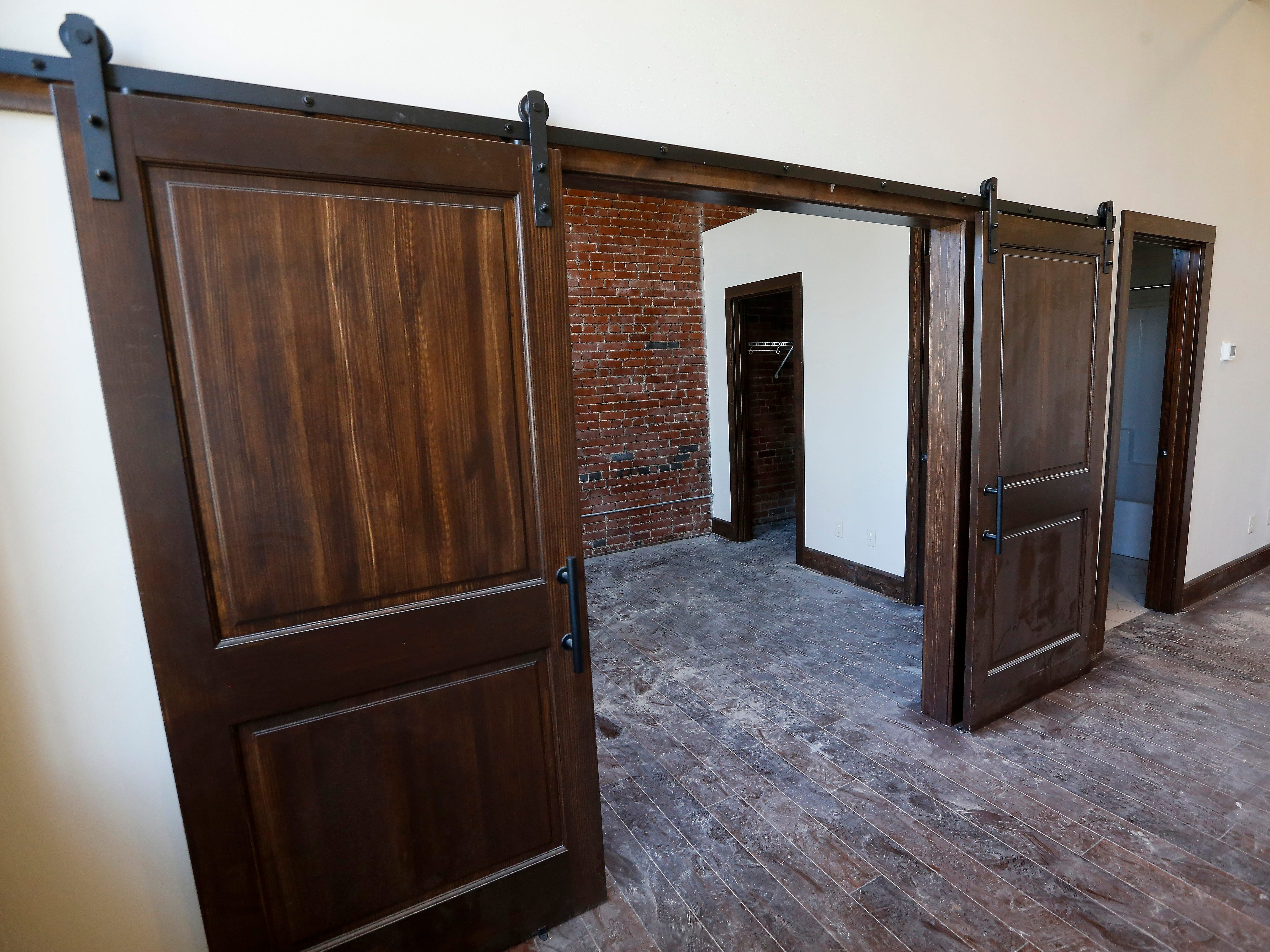 Sliding barn doors open up the space in this apartment on the second floor at the Bailey School Lofts on Central Street near Campbell Avenue.