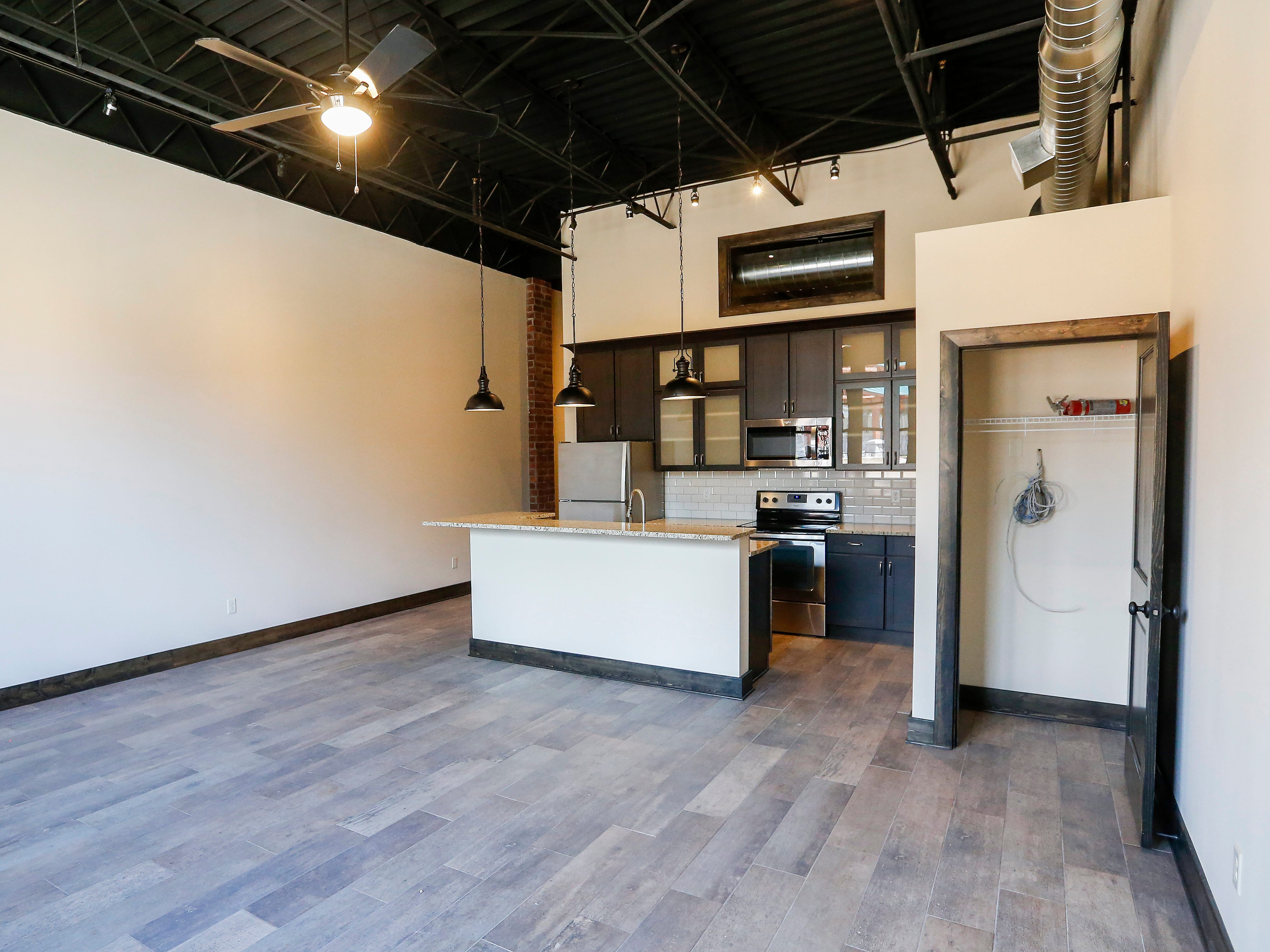 The living room and kitchen area inside one of the 2-bedroom units at the Bailey School Lofts on Central Street near Campbell Avenue.