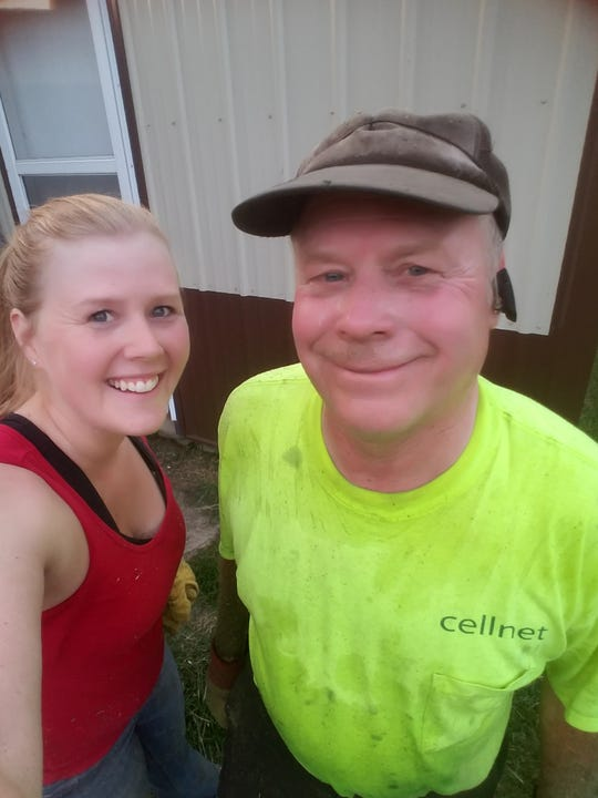 Kimberly and Norbert Walz pose for a photo after unloading hay into the hay barn.