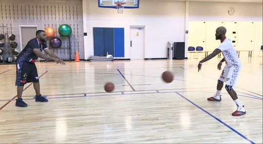 Dominique Farmer works on bounce passes with Caleb Bolton at Premier Health & Fitness Center in Tallahassee.