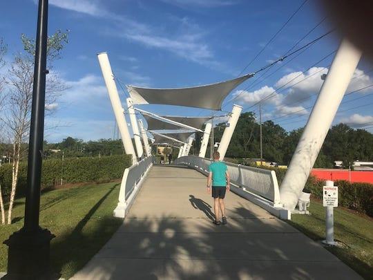Move will walk through the canopied bridge across South Monroe Street on Saturday.