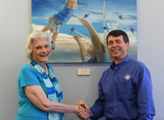 """Barbara Hoffman, left, executive director of the Cultural Council of Indian River County, and Eric Menger, director of the Vero Beach Regional Airport, at the new Art in Public Places installation in the airport's passenger waiting room in front of the painting, """"Teaching the Joy of Flight"""" by artist Merana Cadorette."""