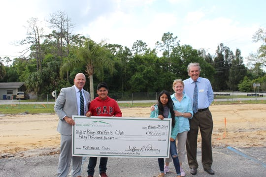Jeff Pickering, left, chief executive officer of the Indian River Community Foundation, presents a $50,000 grant to  Boys & Girls Clubs of Indian River County Executive Director Elizabeth Thomason, board Co-Chairman Bill Munn and two Club Kids.