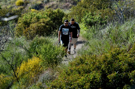 Julian Cardona, of Ventura, and Alex Melendez, of Oxnard, make their way up the Ray Miller Trailhead at Point Mugu State Park on Tuesday. Spring weather and wildflower blooms are bringing people outdoors, raising the chance of rattlesnake encounters.