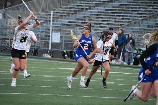 Westlake High junior Shelby Tilton, chased by Newbury Park's Erin Duffy, races up field at Newbury Park High on March 22. Westlake won, 12-9.