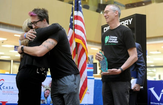 From left, Rachael Watkins, victim services manager, hugs Marcus Grimmie as his father, Bud Grimmie, watches during the ceremony marking National Crime Victims' Rights Week at the Ventura County Government Center. The Grimmie family got the Ellie Liston Hero Award.