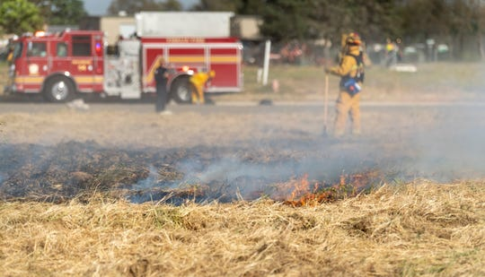 Visalia Fire Department responds to a grass fire in the 9800 block of West Goshen Avenue on Tuesday, April 9, 2019. Two engines and one truck from the City and an engine from the County worked in high winds to suppress the fire that consumed less than an acre of weeds.