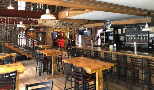 Sawmill Brewing Company in Merrill, WI offers a cabin-like taproom with a stairwell to an upstairs hang-out area.