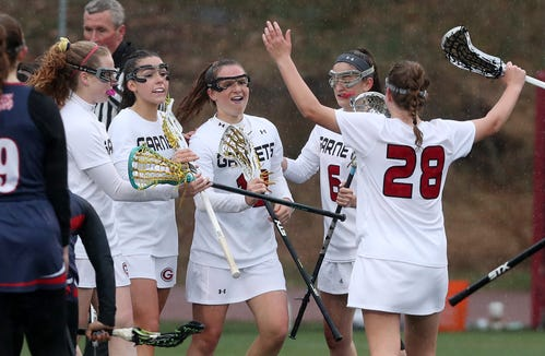 Rye's Ellie Hedges (12), center, celebrates a second half goal with teammates in game against Byram Hills during girls lacrosse action at Rye High School April 9,  2019. Rye won the game 12-9.