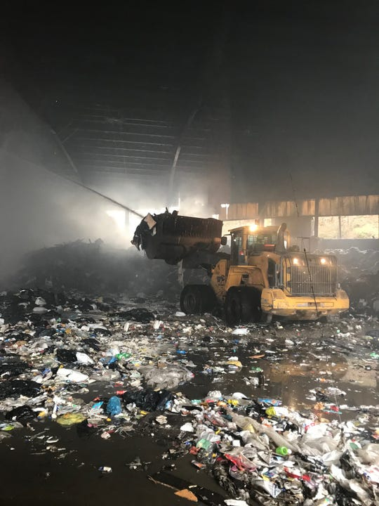 Workers clean up after a fire burned through a Waste Management facility at 325 Yonkers Ave. in Yonkers on April 9, 2019.