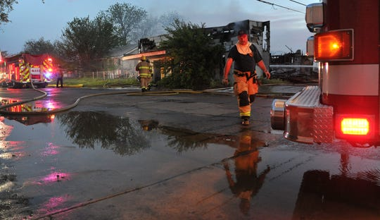 Wichita Falls firefighters begin cleaning up after battling a structure fire at a vacant business, located in the 2200 block of Avenue F, Wednesday morning.