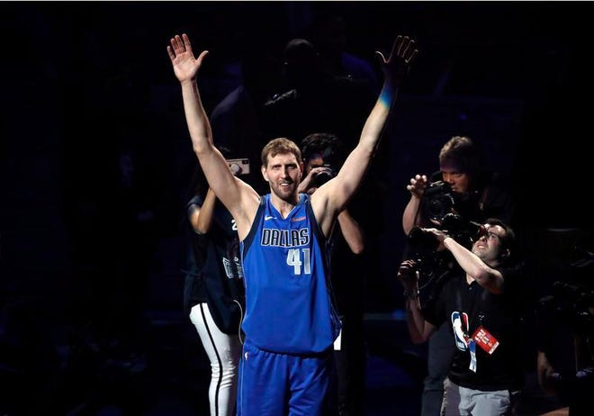 Dallas Mavericks' Dirk Nowitzki acknowledges cheers from fans as he walks off the court following the team's game against the Phoenix Suns in Dallas, Tuesday. The team honored Nowitkzi, who played his final home game of his 21-year career.