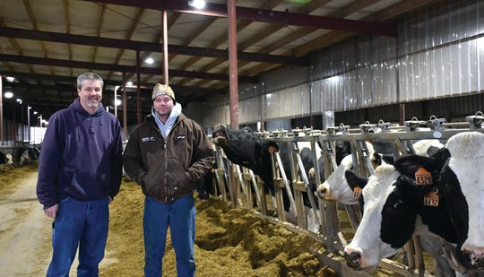 Barry Bubolz, NRCS Area GLRI Coordinator, with Aaron Augustian, of Augustian Farms LLC, inside an Augustian dairy barn.