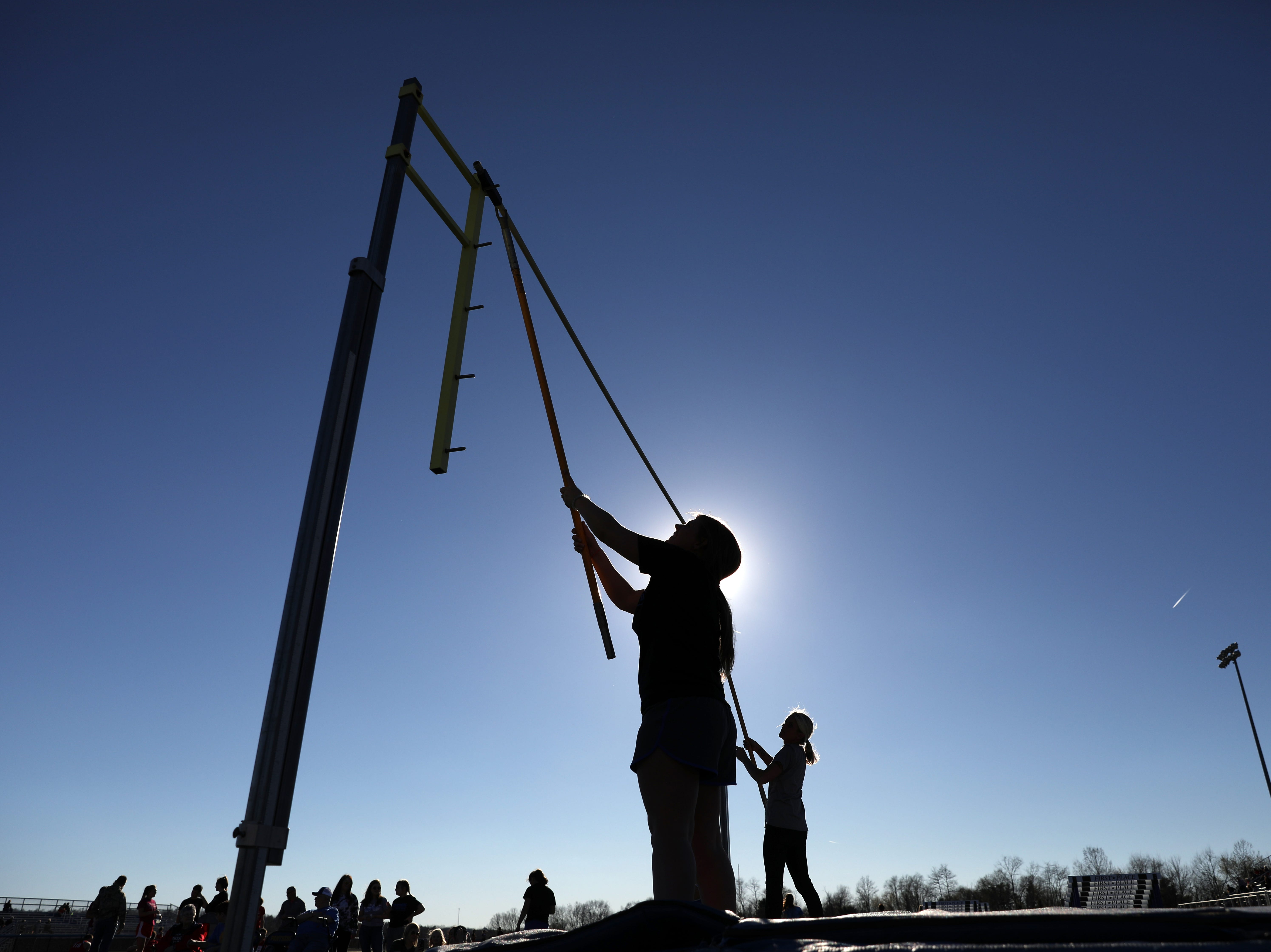 Volunteers reset the bar during the pole vault during Tuesday's tri-meet between Sheridan, New Lexington and host Maysville.