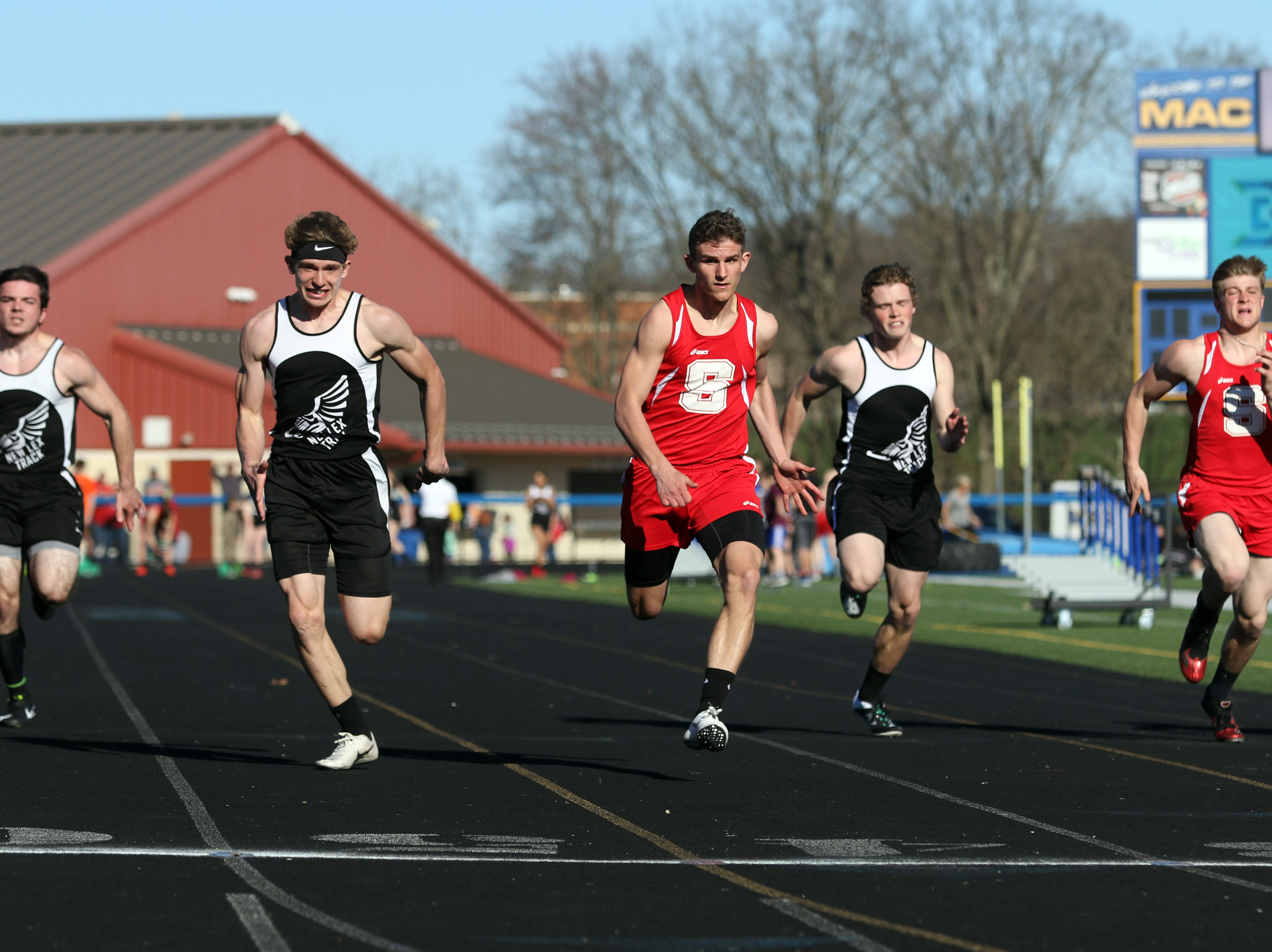 Sheridan's Jacob Rhodes and New Lexington's C.J. Ratliff battle to the end of their heat of the 100 meter dash during Tuesday's tri-meet between Sheridan, New Lexington and host Maysville.