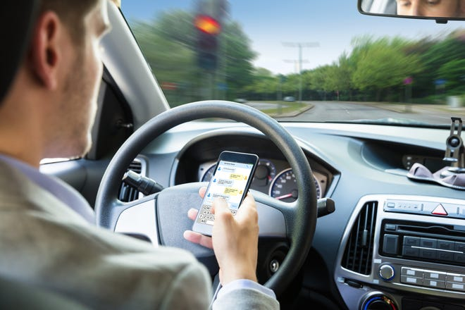 Close-up Of A Person's Hand Sending Text Message By Mobile Phone While Driving Car