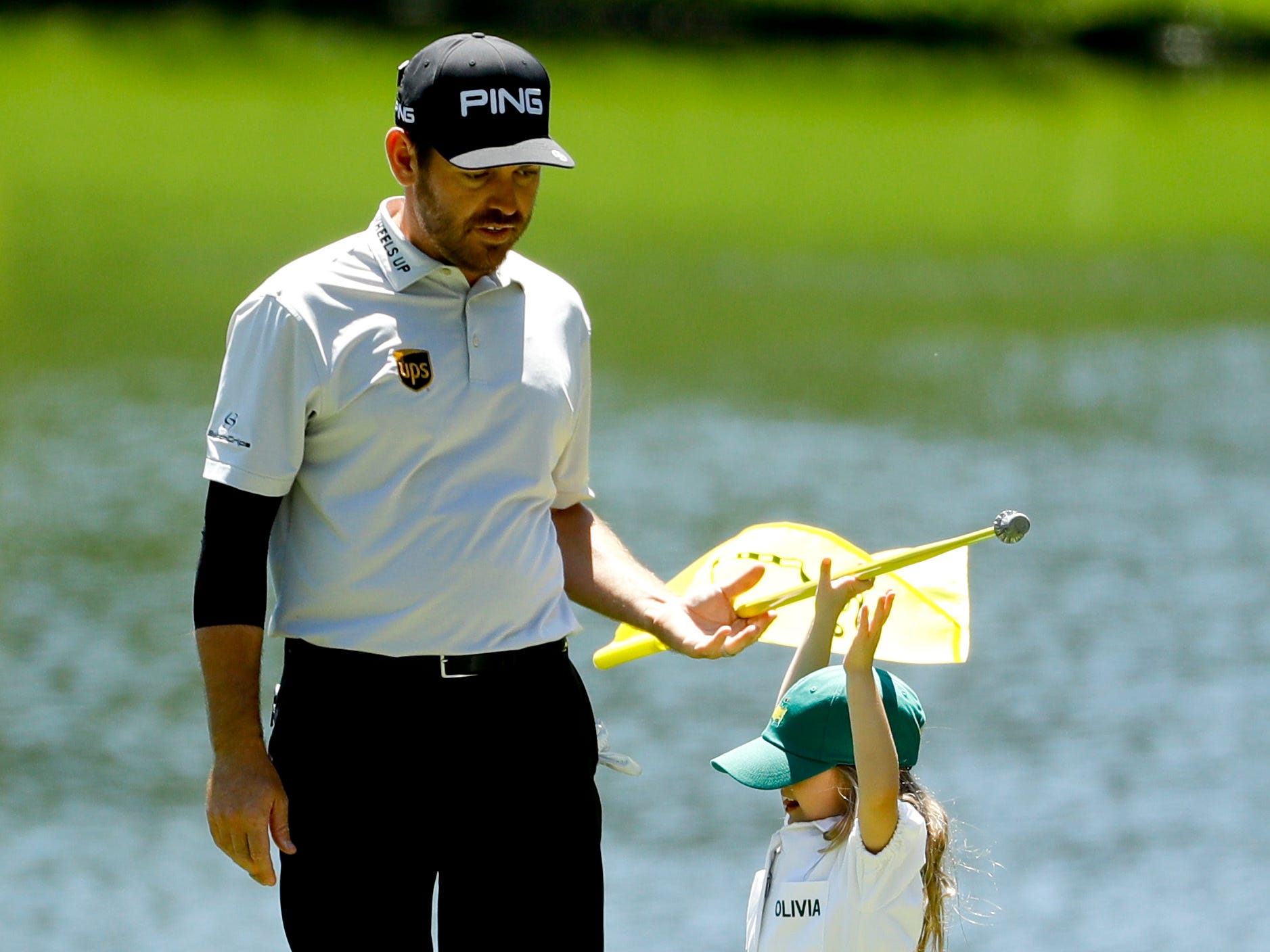 Louis Oosthuizen helps his daughter Olivia with the flag on the third hole.