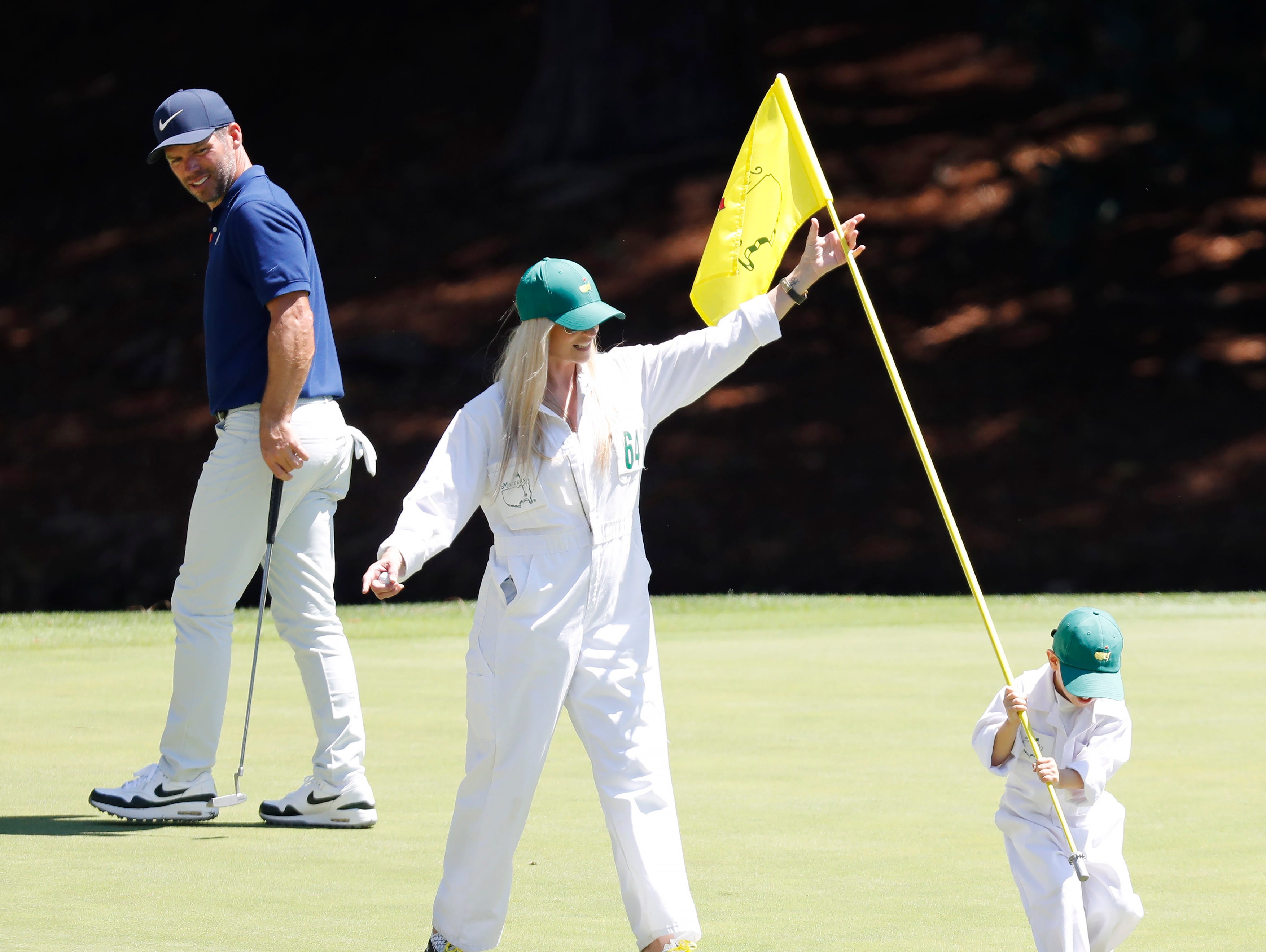 Paul Casey watches as his wife Pollyanna helps their son Lex put the pin flag back on the eighth hole.