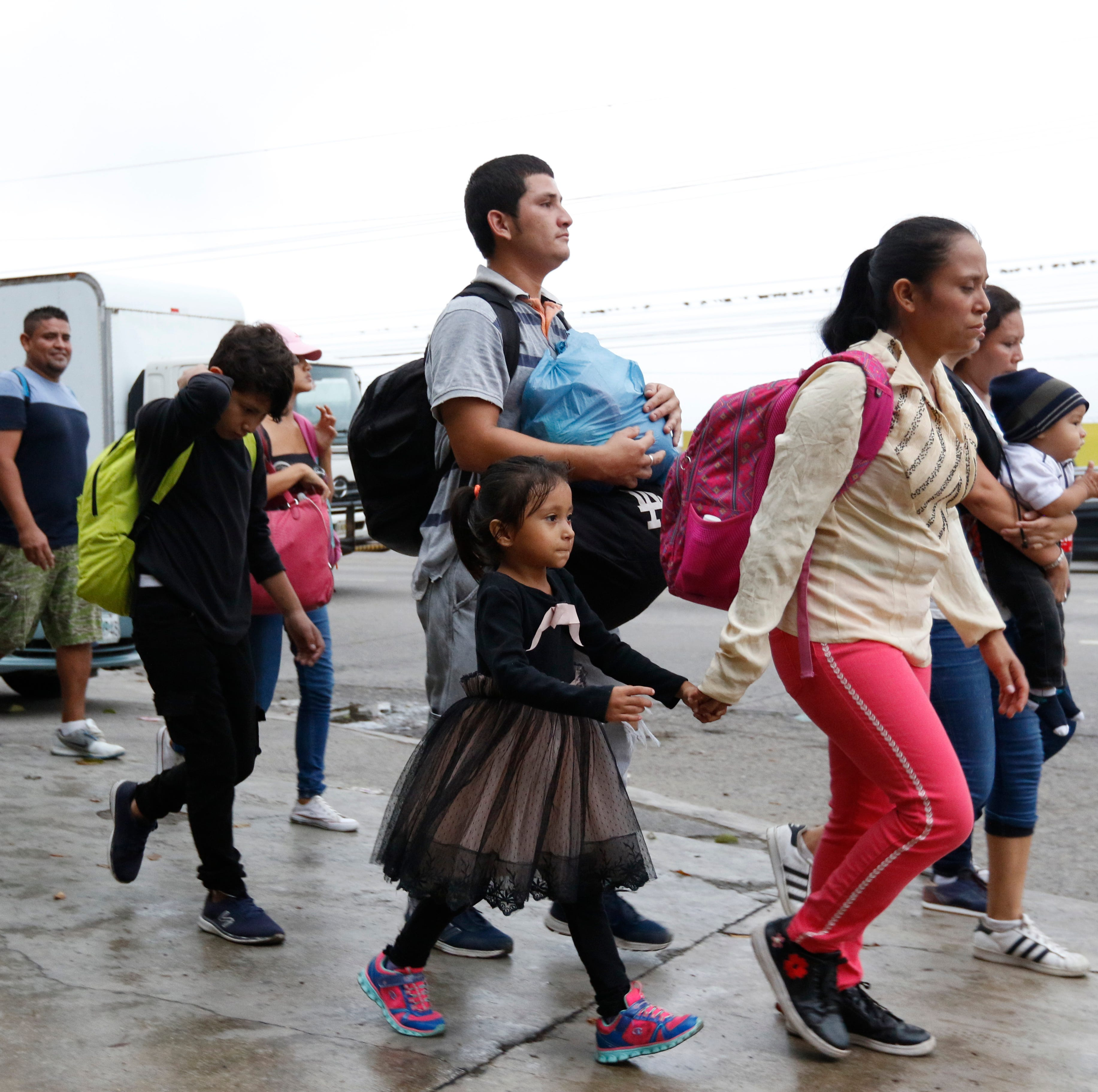 Migrants walk along a highway as a new caravan of several hundred people sets off in hopes of reaching the distant United States, in San Pedro Sula, Honduras, shortly after dawn Wednesday, April 10, 2019. Parents who gathered at the bus station with their children to join the caravan say they can't support their families with what they can earn in Honduras and are seeking better opportunities.