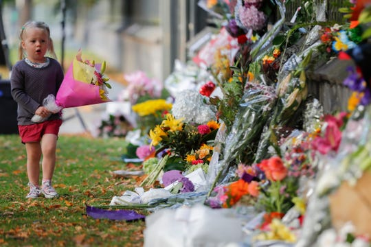 In this March 17, 2019, file photo, a girl carries flowers to a memorial wall following the mosque shootings in Christchurch, New Zealand. New Zealand's parliament on Wednesday passed sweeping gun laws which outlaw military-style weapons, less than a month after the nation's worst mass shooting left 50 dead and 39 wounded in two mosques in the South Island city of Christchurch.