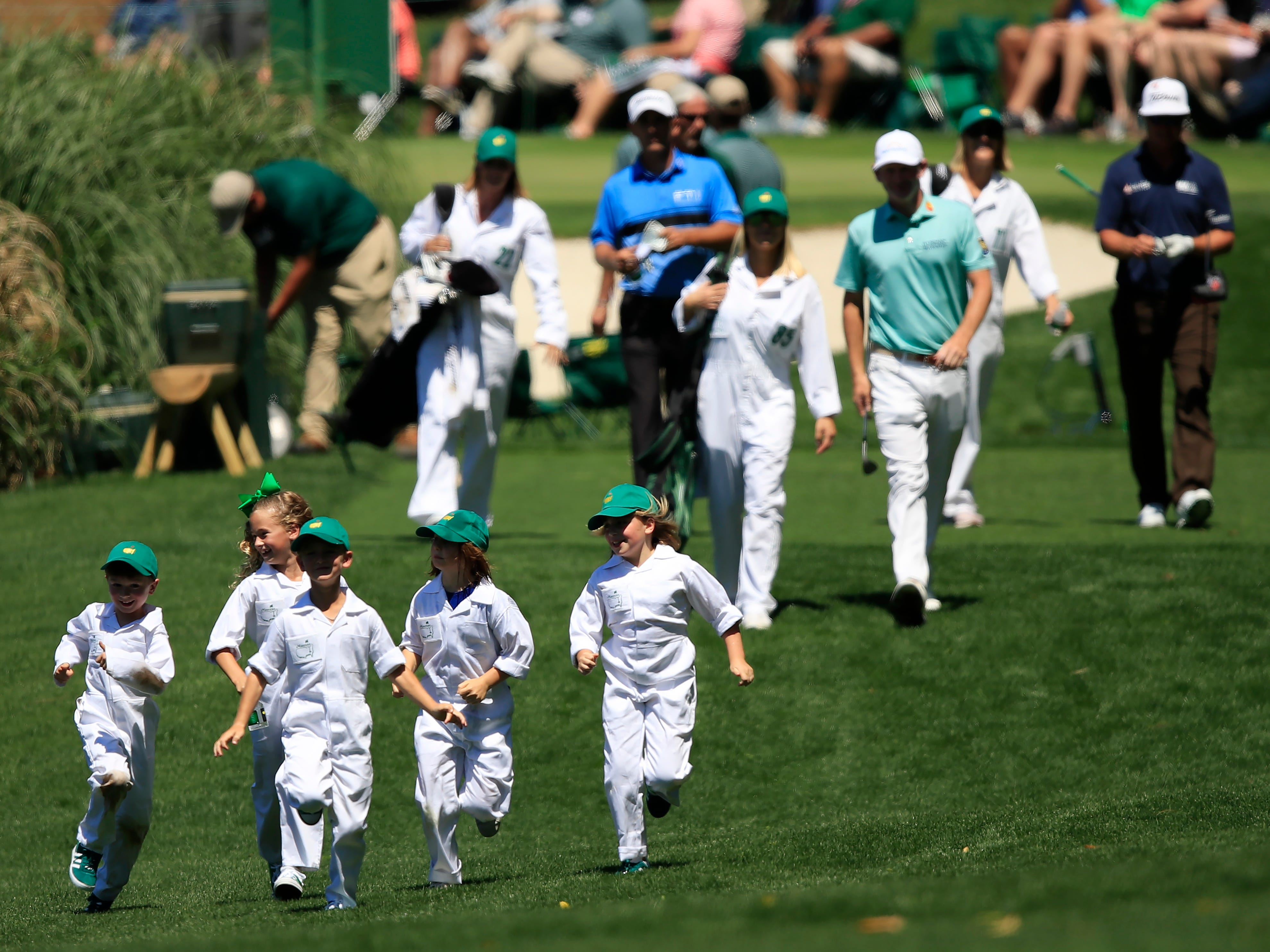 Children with the group of Charley Hoffman, Brandt Snedeker and Charles Howell III run ahead on the fifth hole.