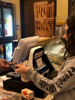 Sydney Baig pays a merchant with her Greenlight Mastercard debit card.
