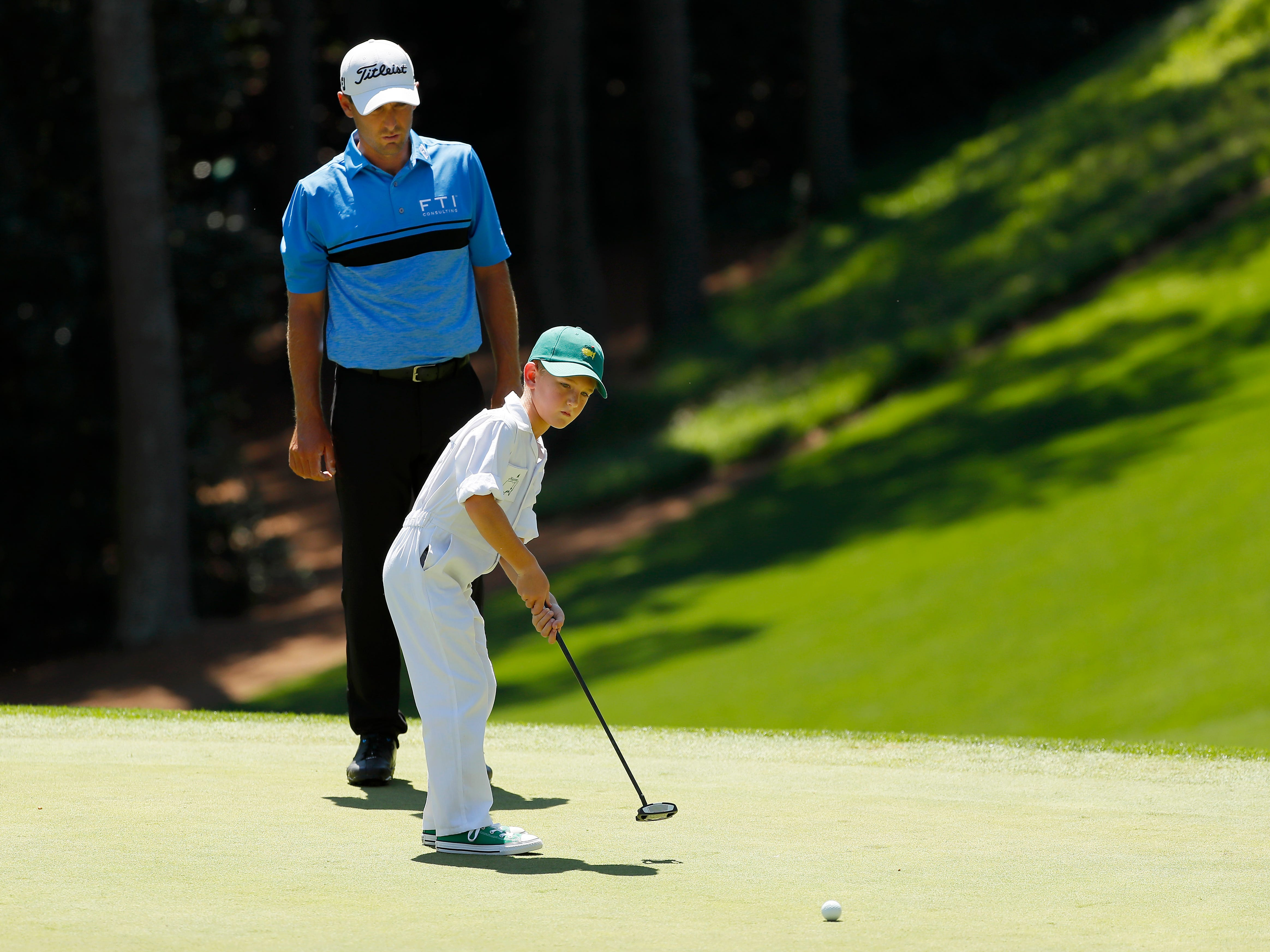 Charles Howell III watches his son Chase putt.