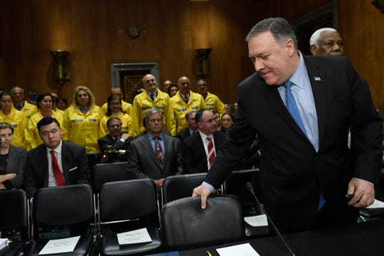 """Members of the Organization of Iranian American Communities stand as Secretary of State Mike Pompeo prepares to testify before the Senate Foreign Relations Committee on Capitol Hill in Washington, Wednesday, April 10, 2019, during a hearing to review the FY 2020 State Department budget request.  The group stood up as a gesture of appreciation for the U.S. designating the Islamic Revolutionary Guard Corps, IRGC, as a """"foreign terrorist organization."""""""