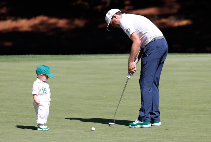 Logan James watches his father Keegan Bradley putt on the eighth hole.