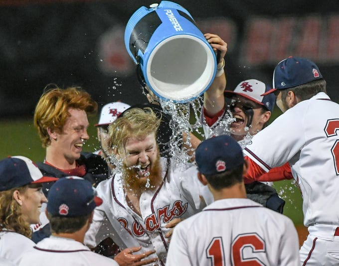 Belton-Honea Path senior Nolan McGonigle (21) is dunked by Belton-Honea Path senior Josh Davis (14) with a bucket of water near players celebrating a Class AAAA Region 1 title with a 7-5 win over Wren in Honea Path Wednesday, April 10, 2019.