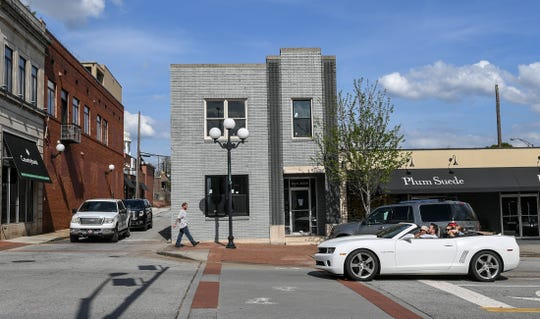 A man walks by a convertible filled with visitors outside the building at 210 North Main St., which will soon have offices and apartments in downtown Anderson.
