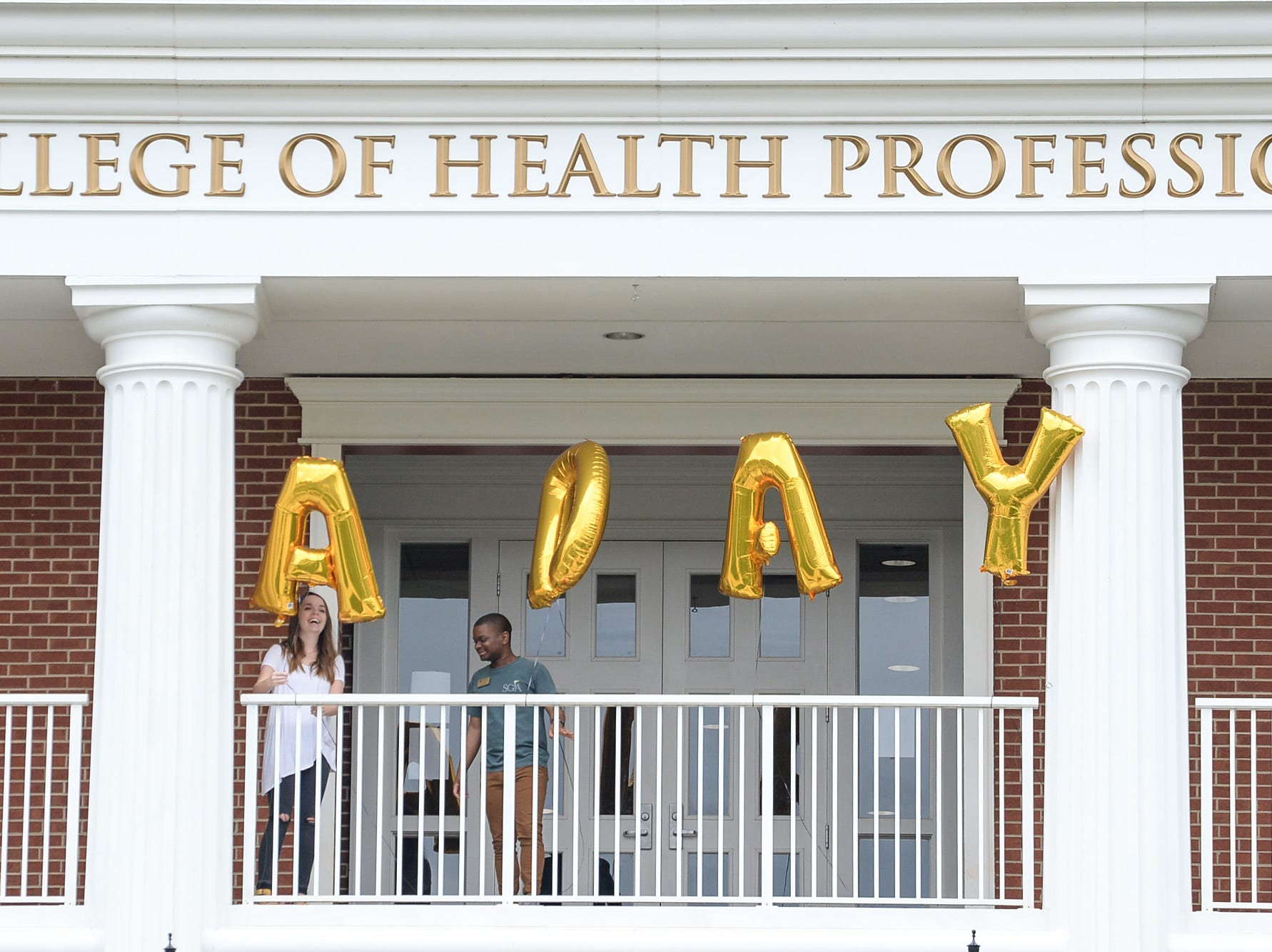 Abigail Carr, left, and Chris Jones, students at Anderson University, plays balloons on the College of Health Profession building during A Day to Give at Anderson University Thursday.  The 24-hour fundraising drive event is meant to give people from the school a chance to participate in events on campus to recognize the past, present, and future.