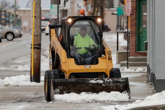 A Manitowoc city employee clears snow and ice off the sidewalk on Franklin Street Thursday, April 11, 2019, in Manitowoc, Wis.