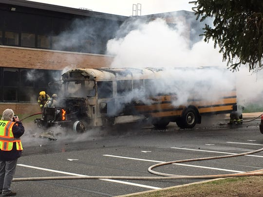 Firefighters put out a burning school bus at Middletown High School North on April 11, 2019.