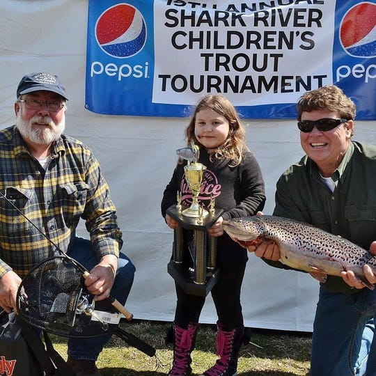 Emily Henderson, 5, center, is the Grand Prize winner of the 2019 Shark River Surf Angler's Children's Trout Contest in Spring Lake. She is flanked by Ken Morse, left, club vice president and Greg Hueth, club president. Hueth holds Henderson's winning fish, a 6-pound 8-ounce brook trout.