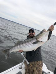 Charles Miller with a striped bass he caught in Raritan Bay. The fish was released according to Chris Massaro, who took the photo.