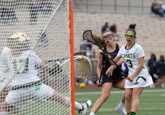 Rumson's Chase Boyle watches as Red Bank Catholic goalie Lindsay Mazzucco blocks her shot.  Rumson/Fair Haven Girls Lacrosse vs Red Bank Catholic in Red Bank, NJ, on April 12, 2019.