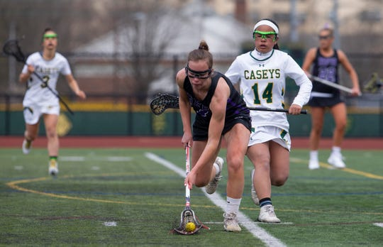 Rumson's Jordan Johnson scoops up a loose ball in first half action. Rumson/Fair Haven Girls Lacrosse vs Red Bank Catholic in Red Bank, NJ, on April 12, 2019.