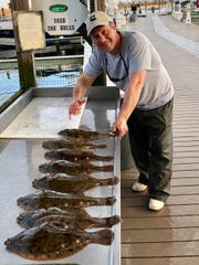 Capt. Kevin Pent of the Johnny Marlin with his fishing party's catch of winter flounder on the Manasquan River.