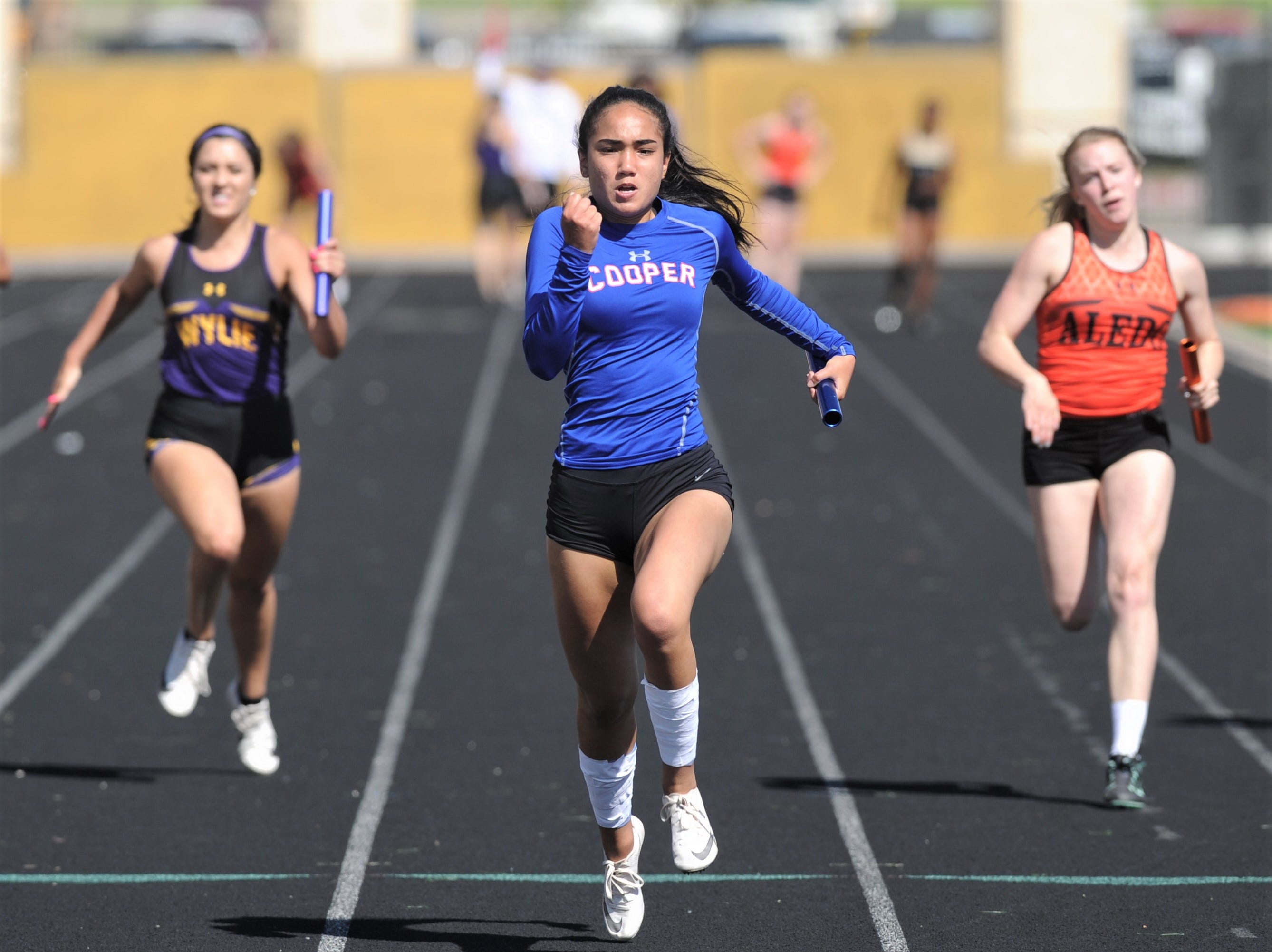 Cooper's Lexa Garcia, center, wins the 400-meter relay while Aledo's Sierra White, left, and Wylie's Madison LaBrenz follow. Garcia and Cooper teammates Kristian Davis, Natashi Hopes and Iyonnia Cherry won the event in 49.98, followed by Aledo (50.91) and Wylie (51.14) at the District 4-5A track and field meet on Thursday, April 3, 2019, at Aledo's Bearcat Stadium.
