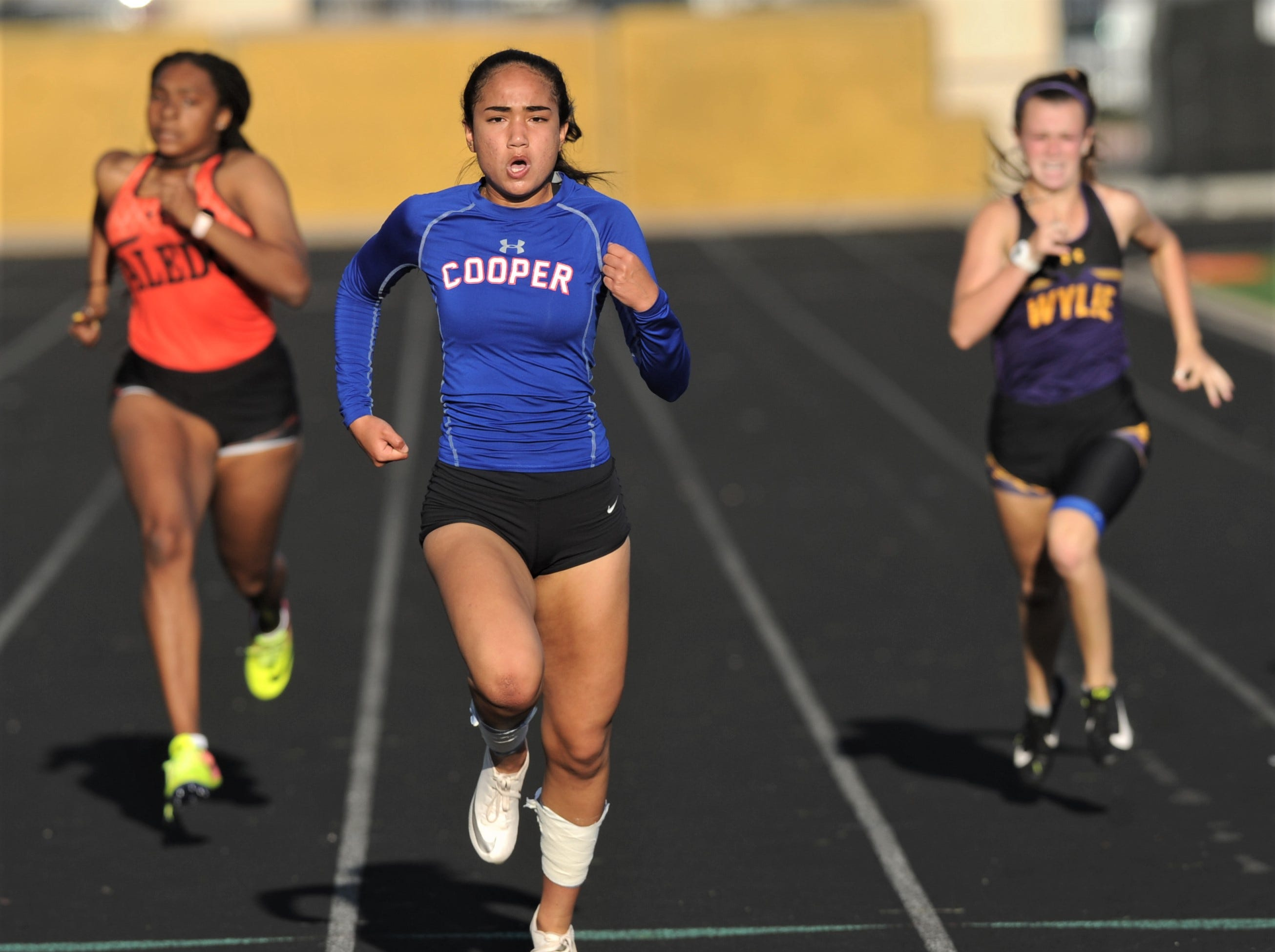 Cooper's Lexa Garcia, center, closes in on the finish line in the 200 meters while being chased by Aledo's Lydia Lawrence, left, and Wylie's Maci Kirk. Garcia won the event in 26.60 seconds. Lawrence was second (27.60), and Kirk was third (27.62) at the District 4-5A track and field meet on Thursday, April 3, 2019, at Aledo's Bearcat Stadium.