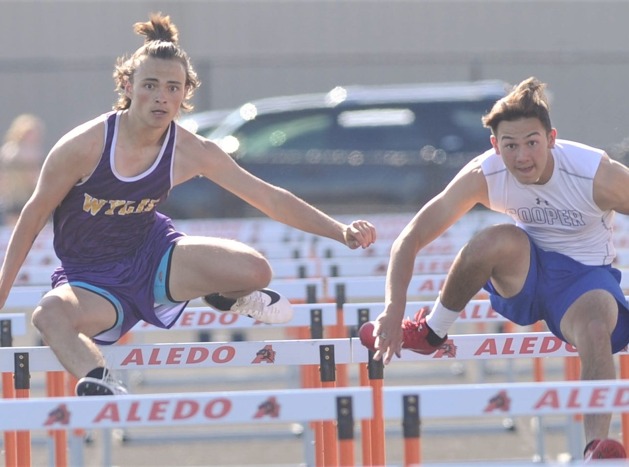 Wylie's Christian Ramirez, left, and Cooper's Justin Deleon eyes the finish in the 110-meter hurdles final at the District 4-5A track and field meet Thursday, April 3, 2019, at Aledo's Bearcat Stadium. Ramirez won the event in 15.55 seconds, while Deleon was second (15.80).