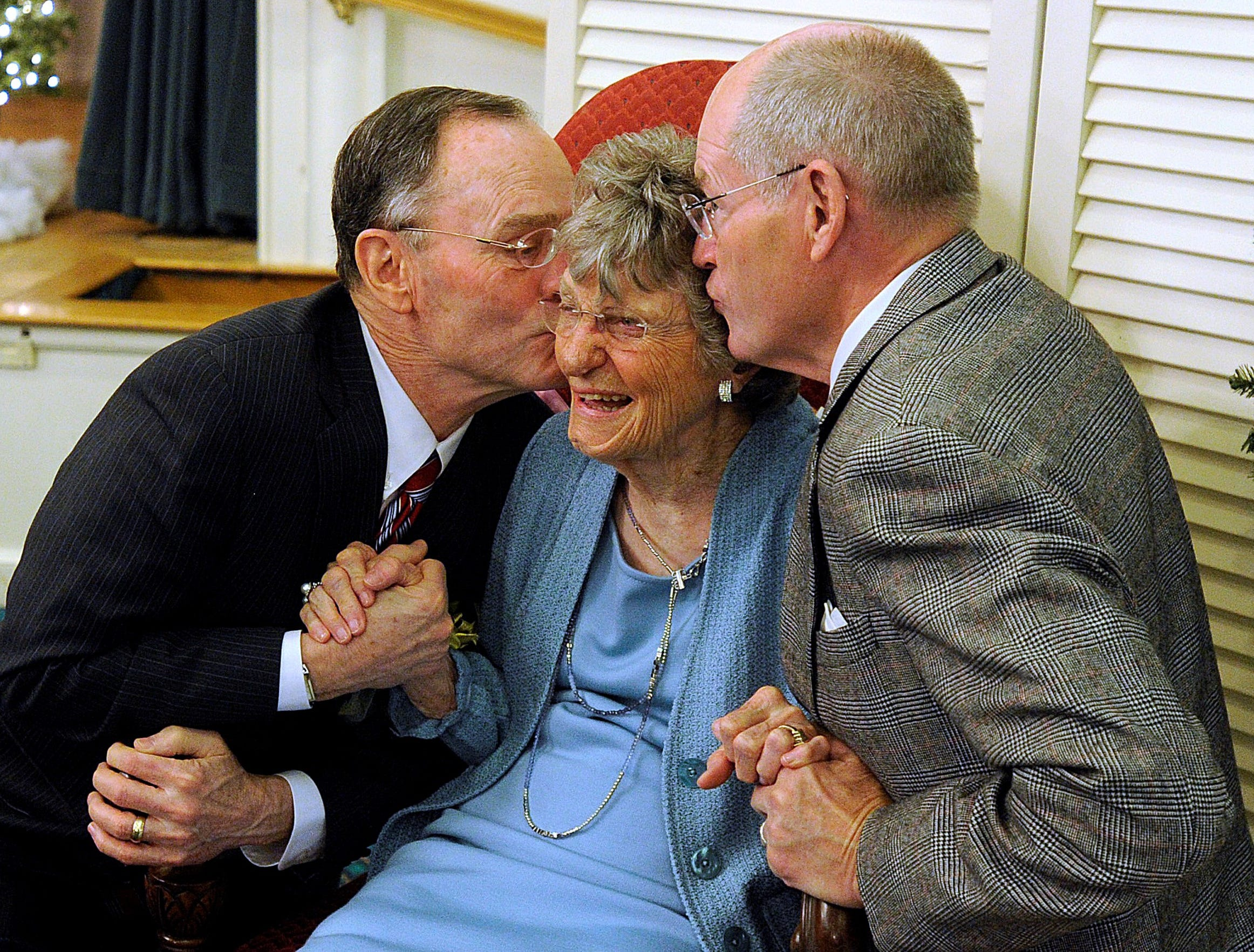 Dr. Virginia Connally gets a kiss on each cheek from Bill Petty (left), of Waco, and Jack Griggs during her 100th birthday party Dec. 8, 2012, at the Abilene Woman's Club.