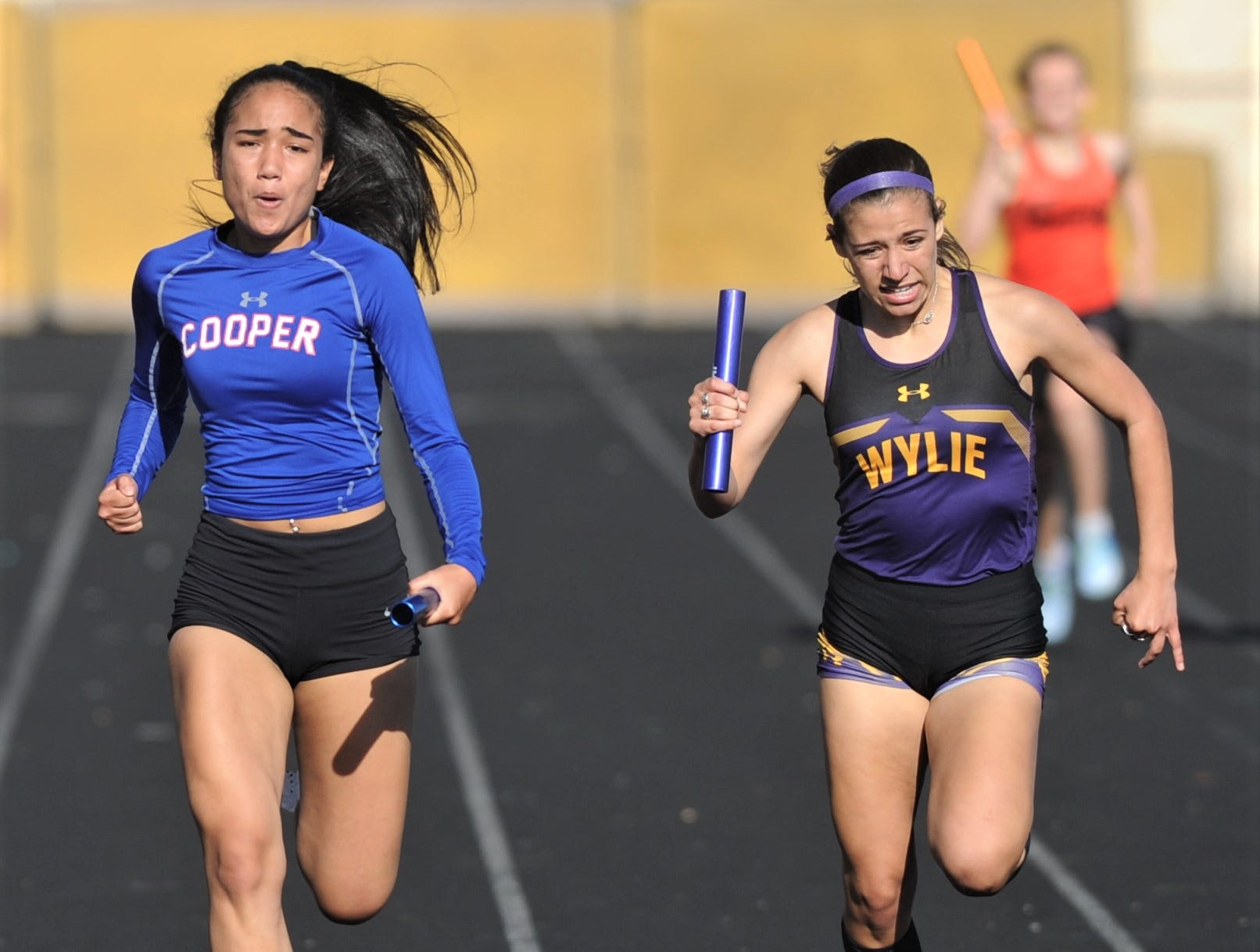 Cooper's Lexa Garcia, left, races Aledo's Sierra White to the finish line on the last leg of the 800-meter relay. Garcia and Cooper won the race in 49.98 seconds, while Aledo was second (50.91) at the District 4-5A track and field meet on Thursday, April 3, 2019, at Aledo's Bearcat Stadium.