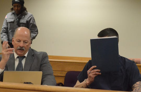 With his attorney, John Sullivan, Craig Cole blocks his face from the camera.
